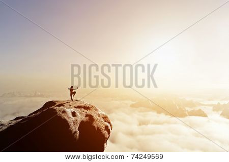 Asian man, fighter practices martial arts in high mountains above clouds at sunset. Kung fu and karate pose. Also concepts of discipline, concentration, meditaion etc. Unique
