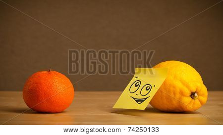 Lemon with sticky note reacting to orange