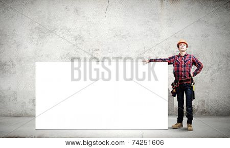 Young builder man in hardhat holding white blank banner
