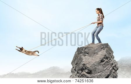 Young woman in casual catching cat with rope