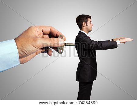 Man recharging a clockwork businessman