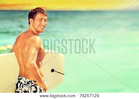 Surfer man going surfing on summer beach. Male bodyboarding surfing man good looking standing with bodyboard surfboard during vacation holidays getaway. Caucasian water sport model in his 20s.