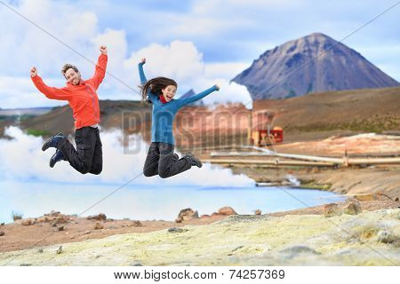 Iceland travel people jumping of joy in front of hot spring and geothermal energy power plant in Namafjall  in Lake Myvatn area. Happy couple on travel in Icelandic nature landscape, Route 1 Ring Road