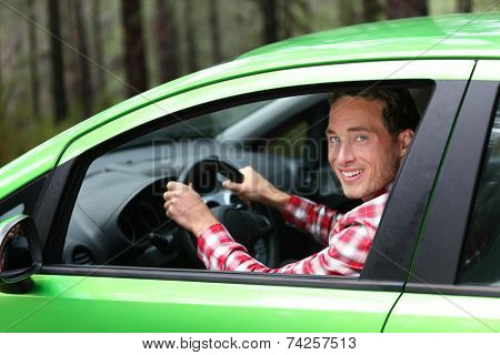 Electric car driver - green energy biofuel concept. Male behind wheel. Man driving new vehicle in cheerful in nature forest. Young male driver looking at camera with arm raised cheering.