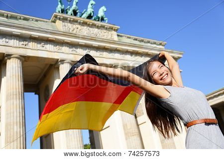 German flag - Woman happy at Berlin Brandenburg Gate cheering celebrating waving flag by Brandenburger Tor, Germany. Cheerful excited multiracial woman in Germany travel concept.