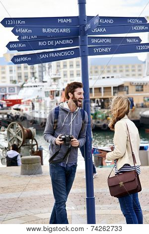 couple on travel holiday at sign with guide book