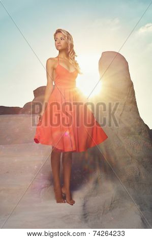 Fashion photo of beautiful lady in red dress in an unusual landscape