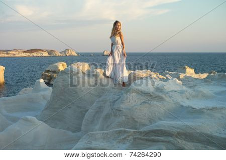 Fashion photo of beautiful lady in white dress in an unusual landscape