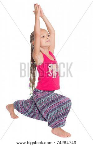 European girl performs gymnastic exercise in Thai dress. The girl is six years old.