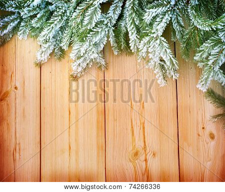 Christmas fir tree covered with snow on wooden  background