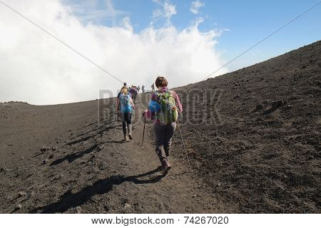ETNA NATIONAL PARK, SICILY, ITALY - OCTOBER 18, 2014: row of hikers going down the steep path of a crater at the border with the area of high criticality of the summit south-east crater.