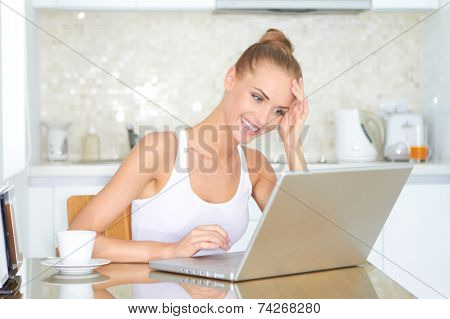 Attractive young woman working on a laptop in the kitchen smiling with delight as she reads information on the screen