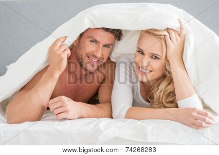 Young couple covering themselves in the duvet peering out from underneath at the camera with playful happy smiles