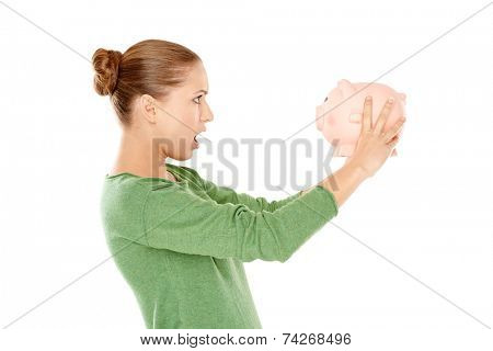 Shocked Young Woman in Green Long Sleeves Shirt Facing Pink Piggy Bank  Captured in Side View. Isolated on White Background.