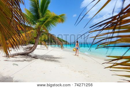 Back view of a young beautiful woman walking along white sand tropical beach