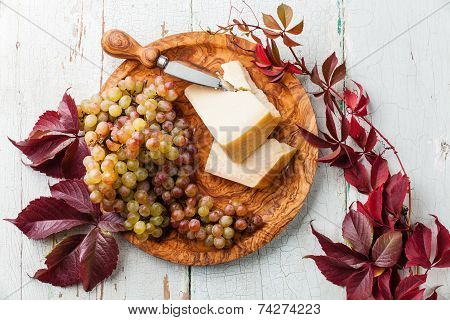 Parmesan Cheese And Grapes On Olive Wood Plate