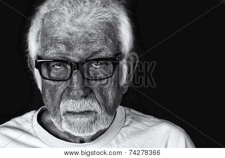 Black and white portrait of an elderly sad man with a tear rolling down his cheek