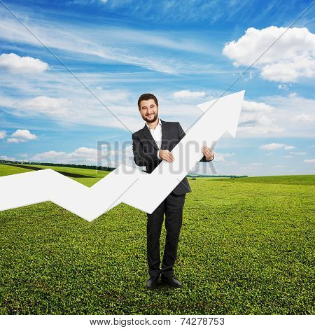 successful businessman standing on the grass and holding white pointer