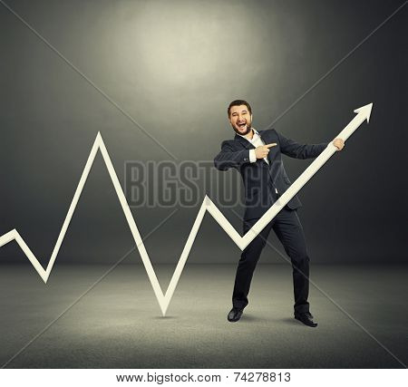 excited businessman pointing at white pointer and screaming. photo in the dark room