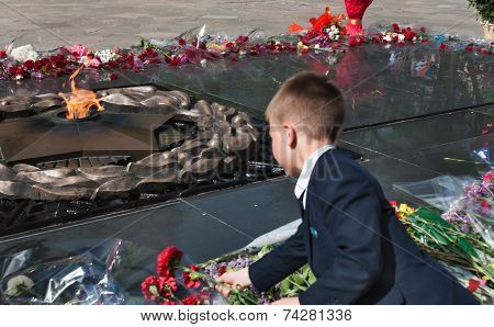 Schoolboy Put Flowers To The Eternal Fire At The Memorial