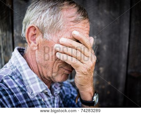 Desperate senior man suffering and covering face with hands in deep depression, pain, emotional disorder, grief and desperation concept