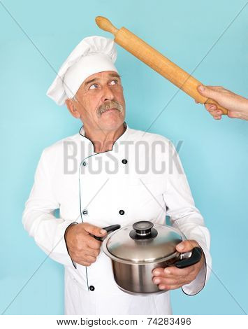 Elderly chef in white cook uniform using rolling pin and getting hit
