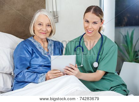 Portrait of smiling senior woman and female caretaker holding tablet PC in bedroom at nursing home
