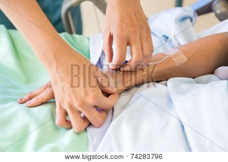 Cropped image of female nurse attaching IV drip on male patient's hand in hospital