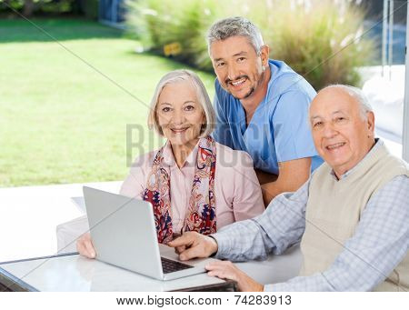 Portrait of smiling male caretaker and senior couple with laptop at nursing home porch