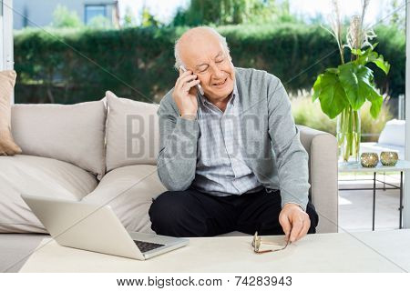 Happy senior man answering smartphone while sitting on couch at nursing home porch