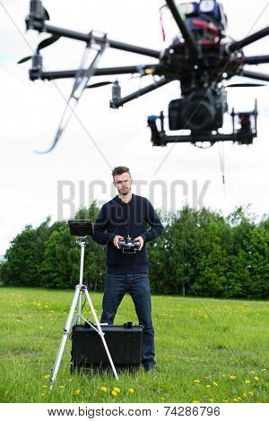Male engineer with remote control flying surveillance drone in park