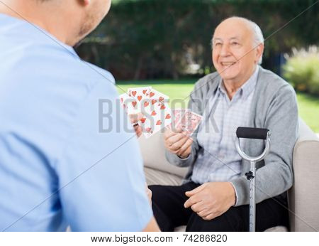 Male caretaker and senior man playing cards while sitting on couch at nursing home porch