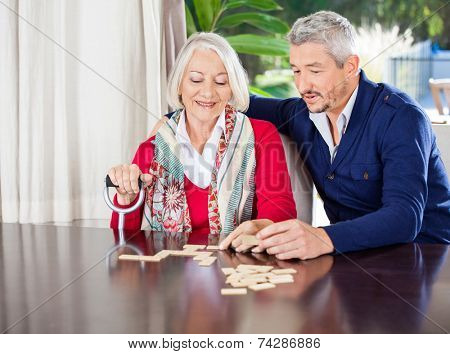 Smiling grandmother playing dominoes with grandson at nursing home