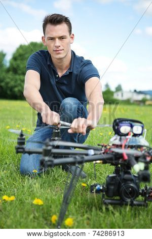 Portrait of confident young engineer fixing propeller of UAV spy drone in park