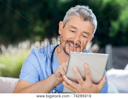 Male caretaker using digital computer while sitting at nursing home porch