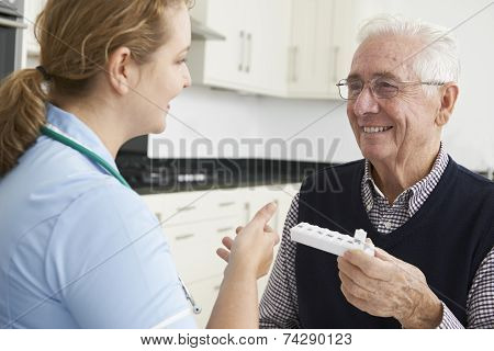 Nurse Helping Senior Man With Medication