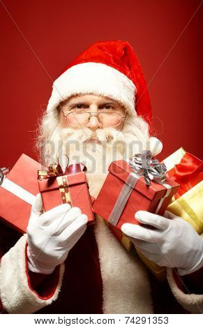 Santa Claus with several red giftboxes looking at camera