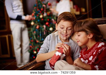 Two siblings opening Christmas gift with their parents decorating fir-tree on background