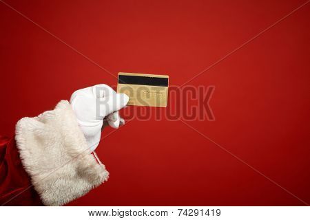Santa Claus gloved hand holding plastic card