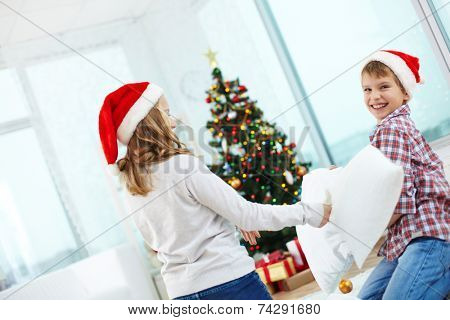 Playful siblings in Santa caps fighting with pillows at home