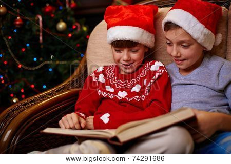 Adorable siblings in Santa caps reading book together on Christmas evening