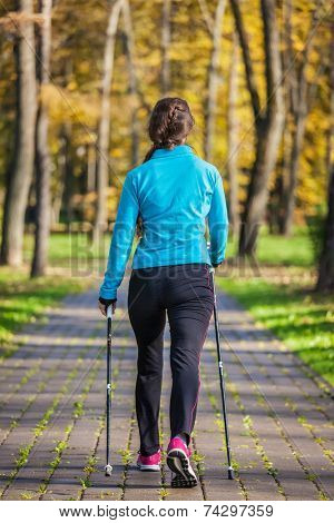 Nordic walking adventure and exercising concept - woman hiking withnordic walking poles in park