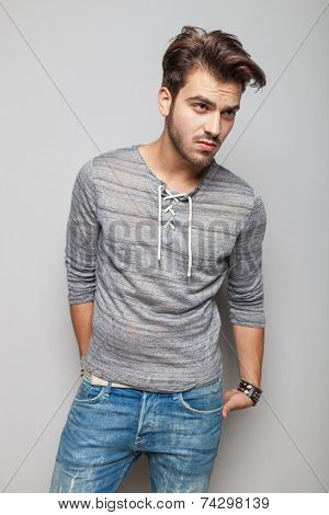 Young fashion man looking away from the camera while holding his hands in his back pocket. On gre background.