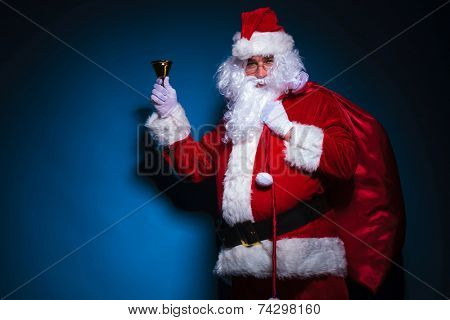 Santa Claus holding his bag on the shoulder and a bell in his hand, against blue backgroud.