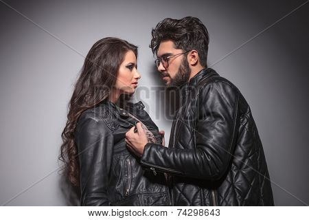 Young fashion couple face to face, the man is pulling his girlfriend leather jacket.