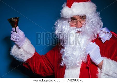 Santa Claus looking at the camera while holding a bell in his right hand.