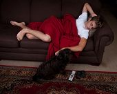 image of couch potato  - A teenage boy laying on a couch with a dog - JPG