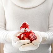 picture of snowman  - Little toy snowman in female hands in cozy mittens - JPG