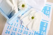 picture of menses  - Sanitary pads in box and sanitary pads and white flowers on blue calendar on light grey background - JPG