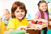 stock photo of classmates  - Boy and his classmates friends looking straight while sitting at desks in classroom during lesson - JPG